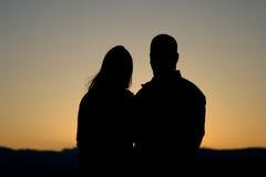 Os pares mostram em silhueta no por do sol Foto de Stock