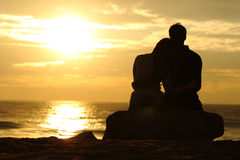 Os pares mostram em silhueta o por do sol de observação na praia Fotografia de Stock
