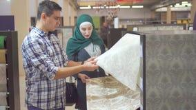 Os pares muçulmanos novos escolhem o papel de parede na loja para o reparo
