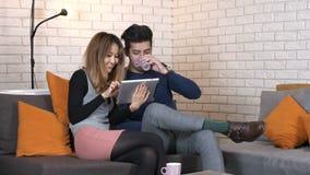 Os pares multinacionais novos felizes que sentam-se no sofá com uma tabuleta e discutem 50 fps filme