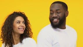 Os pares multirraciais que flertam, amam na primeira vista, isolada no fundo amarelo filme