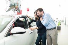Os pares não podem parar de admirar seu carro novo imagens de stock royalty free