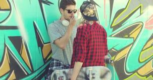 Os pares na moda novos que conversam em um patim estacionam vídeos de arquivo