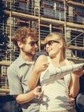 Os pares na parte dianteira da casa nova com modelo projetam-se Fotografia de Stock Royalty Free