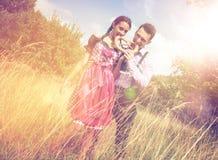 Os pares na roupa bávara comem um brezel fora Foto de Stock Royalty Free