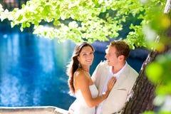 Os pares no amor abraçam no lago do azul da árvore de floresta Fotografia de Stock Royalty Free