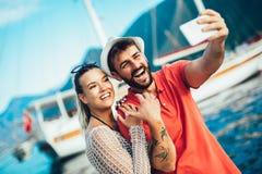 Os pares no amor, apreciando as horas de ver?o pelo mar, fazem a foto do selfie foto de stock royalty free