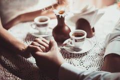 Os pares no amor bebem o café no café, guardando a mão de cada um Imagens de Stock