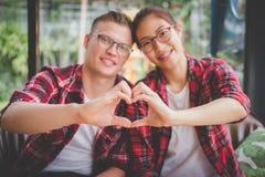 Os pares no amor mantêm a mão unida para formar a forma do coração boyfriend fotos de stock royalty free