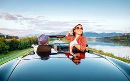 Os pares no amor montam no cabriolet na montanha pitoresca roa foto de stock