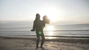 Os pares no amor que roda na praia equipam guardar a mulher em seus braços quando o sol for para baixo no por do sol no movimento vídeos de arquivo