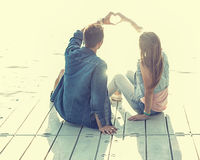 Os pares no amor que senta-se no cais, suas mãos mostram o coração Fotografia de Stock