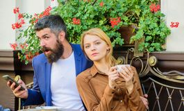 Os pares no amor sentam o terraço do café apreciam o café quando o homem falar o telefone Menina que data com homem de negócios A fotografia de stock