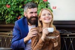 Os pares no amor sentam o terra?o do caf? do abra?o para apreciar o caf? Fim de semana agrad?vel da fam?lia Explore o caf? e luga imagem de stock