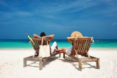 Os pares no branco relaxam em uma praia em Maldivas Fotos de Stock