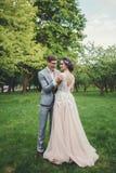Os pares no casamento attire com contra o contexto do parque imagem de stock royalty free