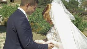 Os pares no casamento attire com um ramalhete das flores e as hortaliças estão nas mãos contra o contexto do campo em filme