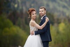 Os pares no casamento attire com um ramalhete das flores e os verdes estão nas mãos de uma cachoeira no por do sol, noiva e fotos de stock royalty free