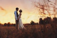 Os pares no casamento attire contra o contexto do campo no por do sol, noivos imagens de stock royalty free