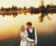 Os pares no casamento attire contra o contexto do campo no por do sol, noivos fotografia de stock