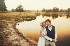 Os pares no casamento attire contra o contexto do campo no por do sol, noivos imagem de stock royalty free
