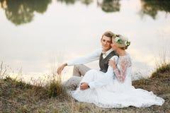 Os pares no casamento attire contra o contexto do lago no por do sol, noivos fotos de stock royalty free