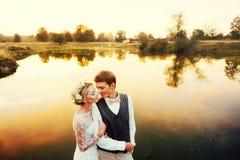 Os pares no casamento attire contra o contexto do lago no por do sol, noivos imagens de stock royalty free