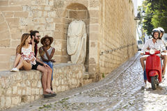 Os pares no 'trotinette' montam os amigos passados que sentam-se em uma parede, Ibiza Fotos de Stock Royalty Free