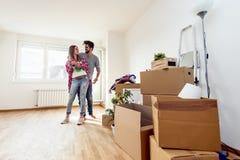 Os pares novos apenas moveram-se no apartamento vazio novo que desembala e que limpa - internamento foto de stock
