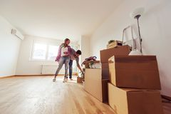 Os pares novos apenas moveram-se no apartamento vazio novo que desembala e que limpa - internamento fotografia de stock