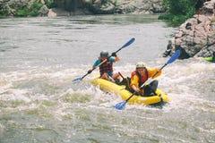 Os pares novos apreciam a ?gua branca que kayaking no rio imagens de stock