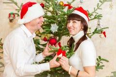 Os pares novos aproximam a árvore de Natal em casa Fotografia de Stock