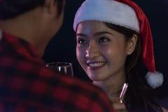 Os pares novos asiáticos Santa com vidros do champanhe olham junto Imagens de Stock