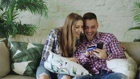 Os pares novos atrativos com smartphone e a compra do cartão de crédito no Internet sentam-se no sofá na sala de visitas em casa imagens de stock royalty free