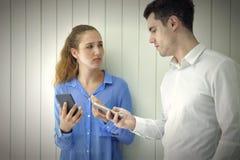 Os pares novos caucasianos têm um descontentamento do problema sobre o telefone celular, conversação séria fotografia de stock royalty free