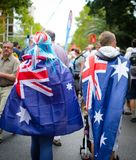 Os pares novos cobrem acima eles mesmos com as bandeiras australianas e o passeio em torno da cidade no dia de Austrália fotos de stock