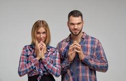 Os pares novos com as caras insidiosos e sorrindo sorriem e algo concebeu desonesto fotos de stock royalty free