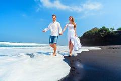 Os pares novos correm pela praia preta da areia ao longo da ressaca do mar imagem de stock
