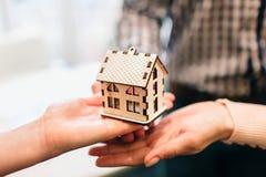 Os pares novos da família compram bens imobiliários da propriedade do aluguel Agente que dá a consulta ao homem e à mulher Contra imagens de stock royalty free