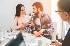 Os pares novos da família compram bens imobiliários da propriedade do aluguel Agente que dá a consulta ao homem e à mulher Contra fotos de stock