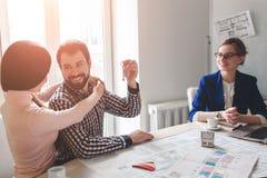 Os pares novos da família compram bens imobiliários da propriedade do aluguel Agente que dá a consulta ao homem e à mulher Contra foto de stock royalty free