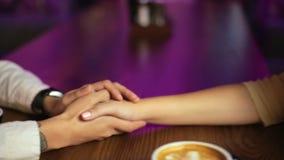 Os pares novos de amantes estão sentando-se em um café, bebendo o café que as mãos de sorriso felizes se fecham acima video estoque