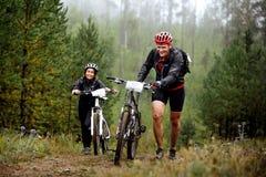 Os pares novos de ciclistas vão subida com seu mountainbike imagem de stock
