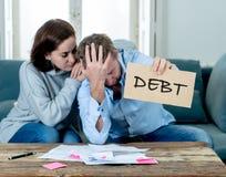 Os pares novos desesperados que mostram o sinal do débito que tem o sentimento financeiro dos problemas forçaram contas pagando imagens de stock royalty free