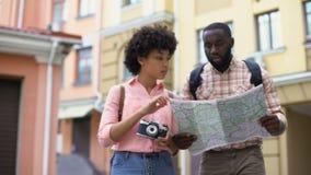 Os pares novos do turista com a câmera do mapa e da foto, escolhendo o sentido, viajam vídeos de arquivo