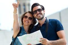 Os pares novos do turista usam seu mapa e apontar aonde querem fotografia de stock
