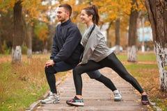 Os pares novos dos esportes vão dentro para esportes no parque do outono que faz um exercício de investem contra em um pé foto de stock royalty free