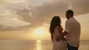 Os pares novos em abraços do amor, olham junto para a frente ao por do sol pelo mar Vista traseira vídeos de arquivo