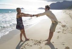 Os pares novos enganam ao redor na praia Fotos de Stock Royalty Free