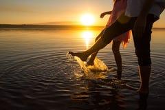 Os pares novos est?o andando na ?gua na praia do ver?o Por do sol sobre o mar Duas silhuetas contra o sol Os p?s fazer espirram d imagens de stock